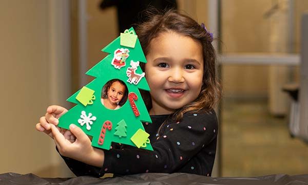 child holding a handmade Christmas tree ornament