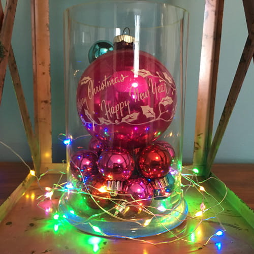 tin lantern decorated with bright pink and blue ball Christmas ornaments inside a glass jar with colored lights