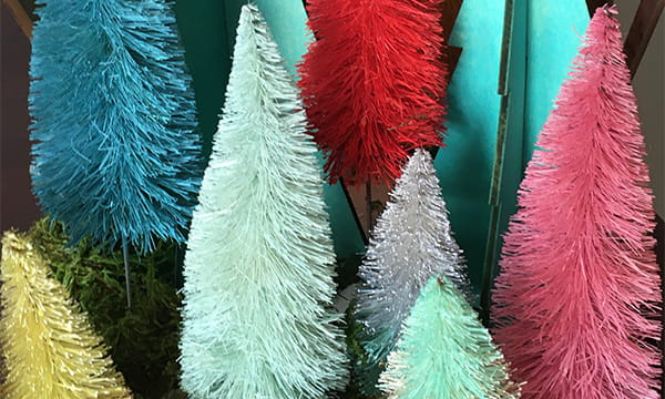 closeup of blue, pink, red, yellow, and green bottle brush Christmas trees