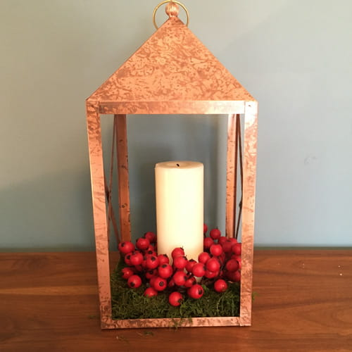 tin lantern filled with a white candle, red wooden cranberries and dried green moss