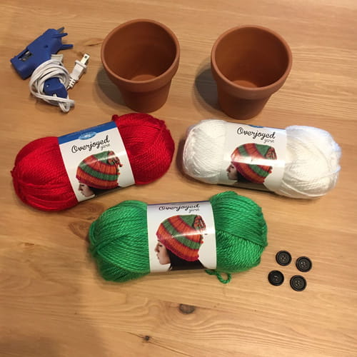 Skeins of red, white, and green yarn; 2 terra cotta plant pots, glue and glue gun, 4 black buttons