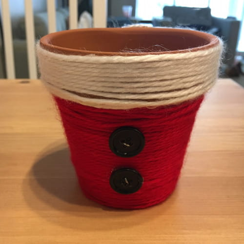 terra cotta pot decorated with red and white yarn to look like Santa Claus