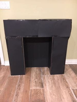two trifold cardboard posters with two cardboard boxes on top - black