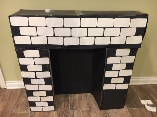 white bricks taped on black trifold cardboard posters/boxes