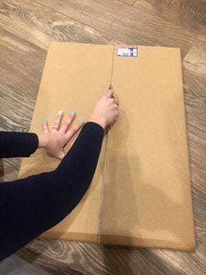 using box cutter to cut cardboard poster board