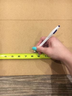 marking desired length on cardboard box with tape measure