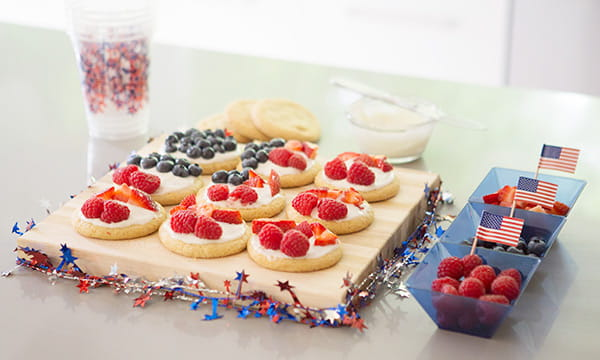 wood cutting board with 3 rows of 3 sugar cookie with white frosting, red raspberries and blueberries. A dish with 3 compartments holding raspberries and blueberries and small USA flags is next to the board.