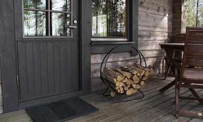 firewood stacked in round holder on porch