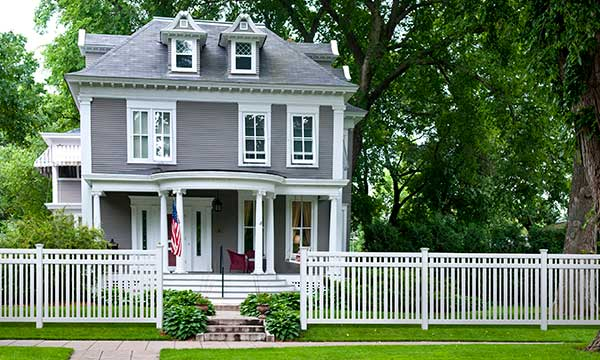 outdoor essentials pro series evanston white vinyl picket fence in front of tall gray house with trees and grass