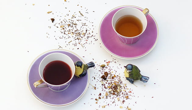 cup of tea on pink saucer and cup of tea on purple saucer with scattered dried tea
