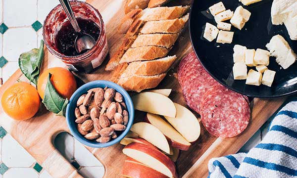 wood cutting board with cheese cubes, sliced apples, sliced baguette, sliced salami, almonds, red jam and oranges