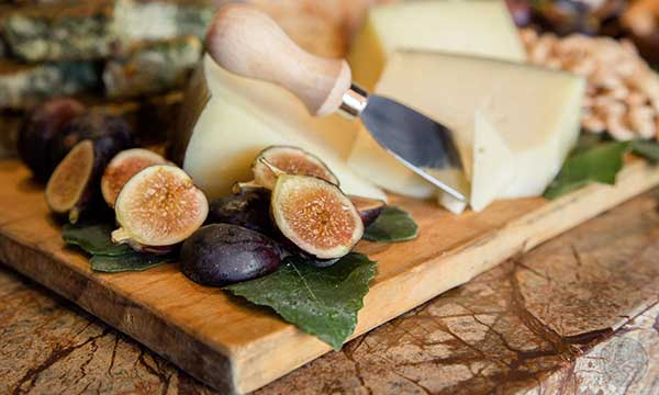 wood cutting board with cheese wedges, cut figs, and serving knife