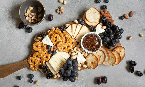 wood paddle with cheeses, toasted bread slices, pretzels, fig jam, blackberries, black grapes, pistachios, almonds