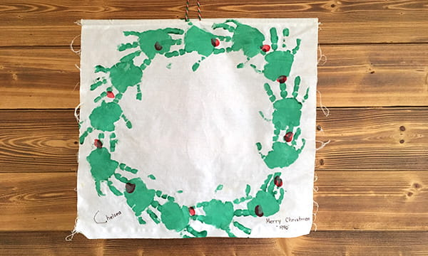 white material with child's green handprints forming a Christmas wreath on a wood background