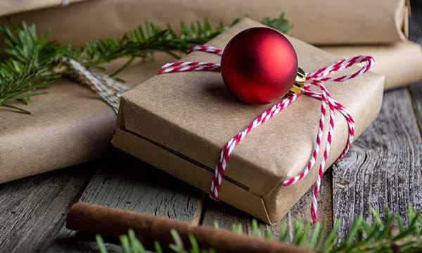 Christmas gifts wrapped in brown paper with red ornament