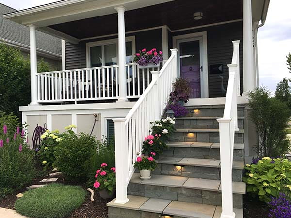 gray house with purple door, flower pots lined on stairs leading to porch