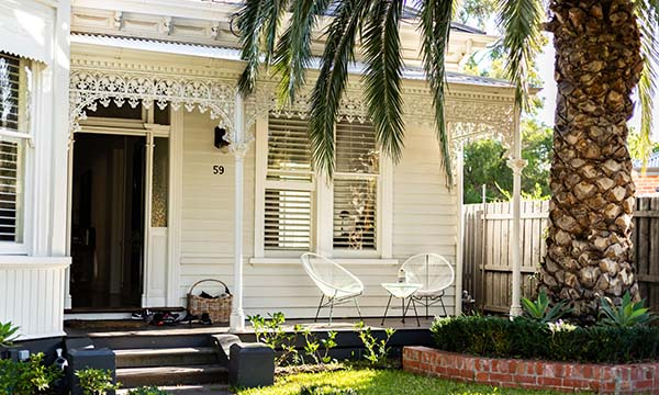 white cottage with 2 white chairs on porch, large palm tree with brick edging