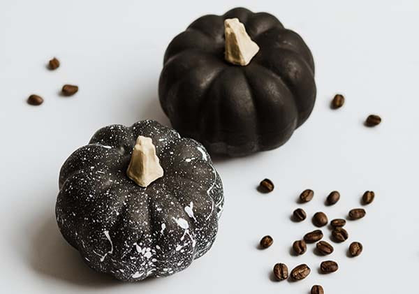 2 small pumpkins painted black with white paint splatters
