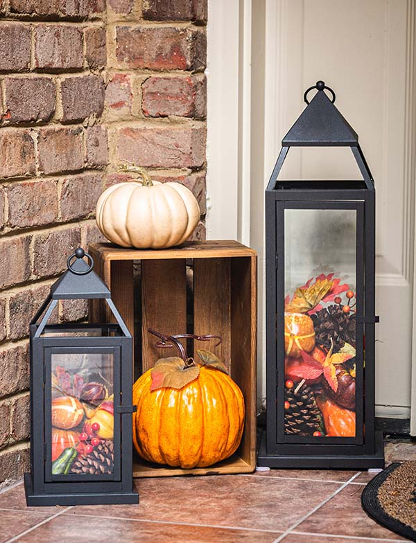 Doorstep with pumpkins and 2 black lanterns filled with tiny pumpkins and pinecones