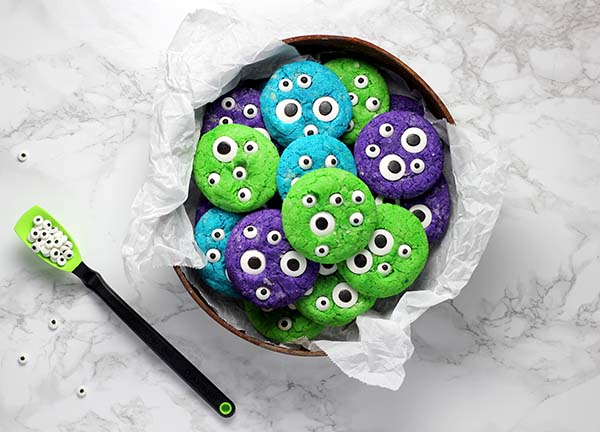 plate of green, turquoise and purple cookies with candy eyes