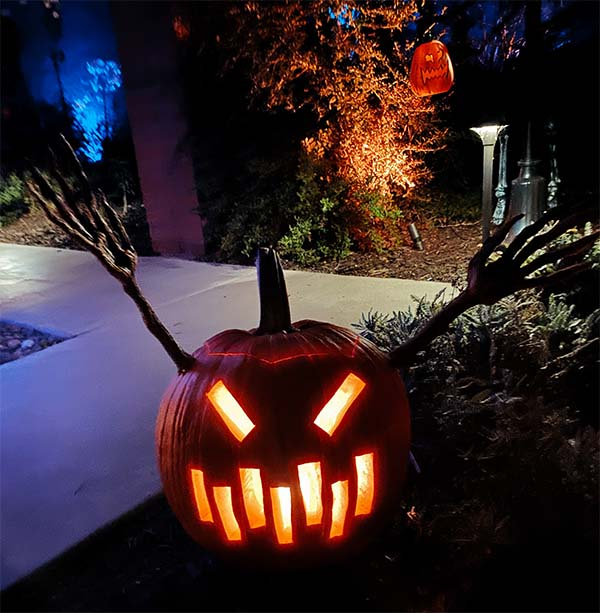 jack-o'-lantern lit at night with cut-out rectangles forming eyes and mouth.
