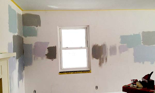 room with swatches of different shades of gray paint on white walls