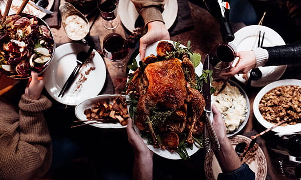 Thanksgiving dinner with roast turkey and side dishes being served on table