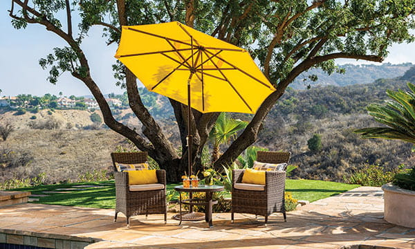 Yellow patio umbrella, 2 wicker chairs and dining table underneath tree by pool, with hills in the background