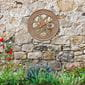 Medallion copper thermometer on stone wall in garden