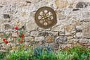 Medallion french bronze thermometer on stone wall in garden