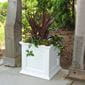 purple and green plants planted inside the white ferndale square planter box outdoors in between two columns.
