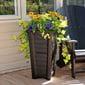 long green plants with orange flowers planted inside the black huron tall planter on a deck.