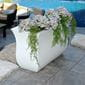 long, green plants and white flowers planted inside the white hillsdale rectanglular planter next to a pool.