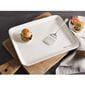 White platter with spatula and burger on cutting board next to plate with burger and napkin.