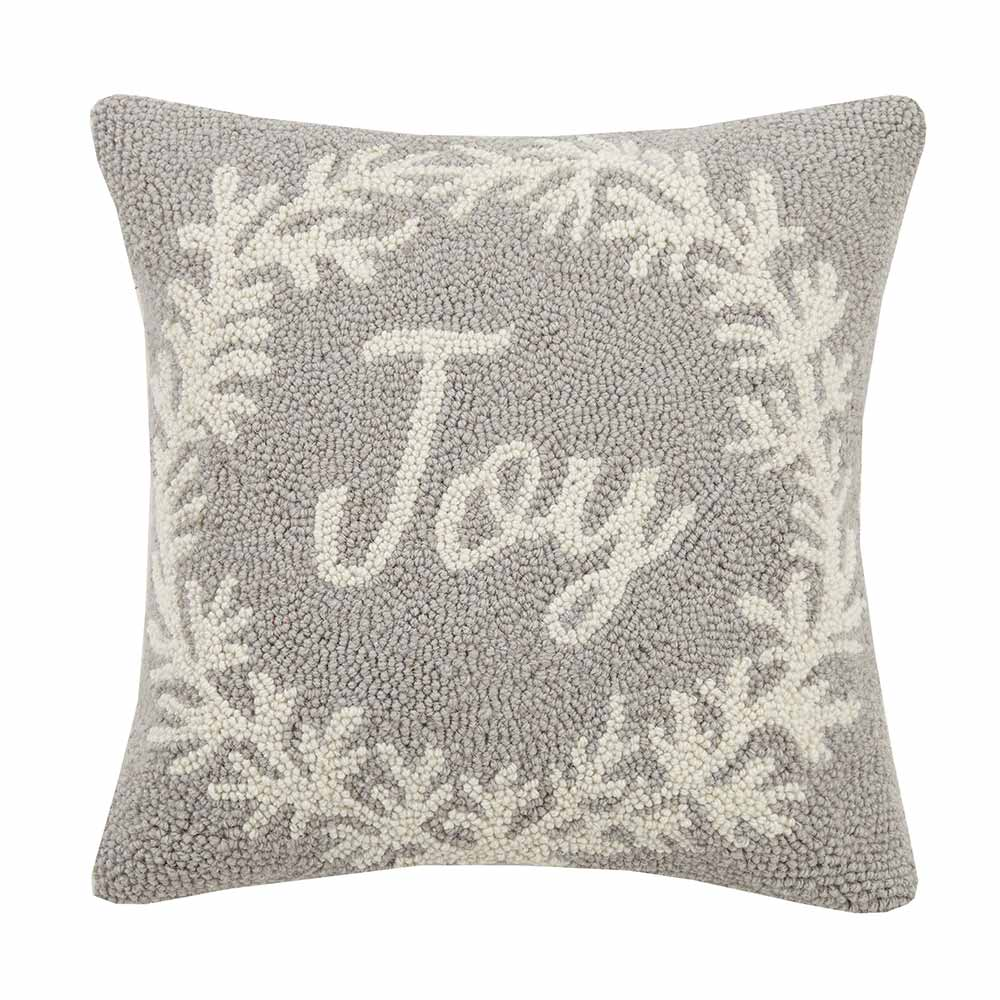 Gray square pillow with white wreath around the word