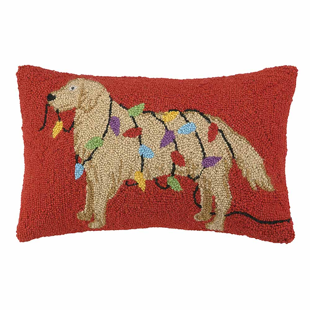 Red rectangular pillow with gold dog wrapped in Christmas lights on it.