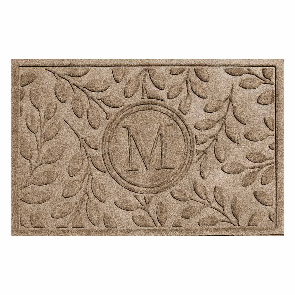 Tan rectangular mat with leaf patterns and letter M in the middle