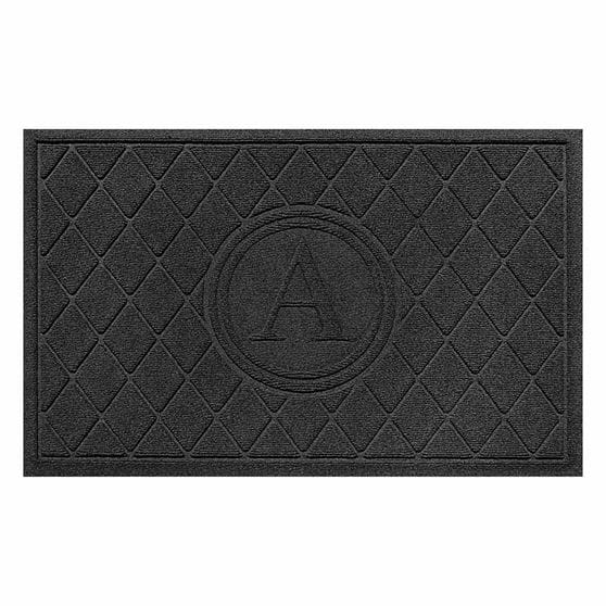 Black rectangular mat with diamond pattern and giant letter