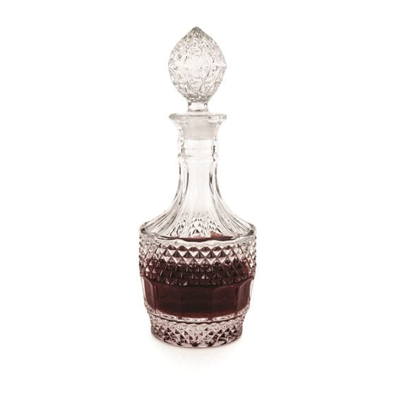 Crystal vintage decanter with liquid contents and a white background