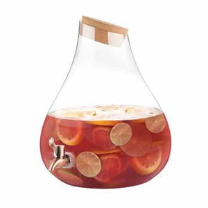 Red sangria with lemon and lime slices in teardrop-shaped glass drink dispenser with cork lid and metal spigot