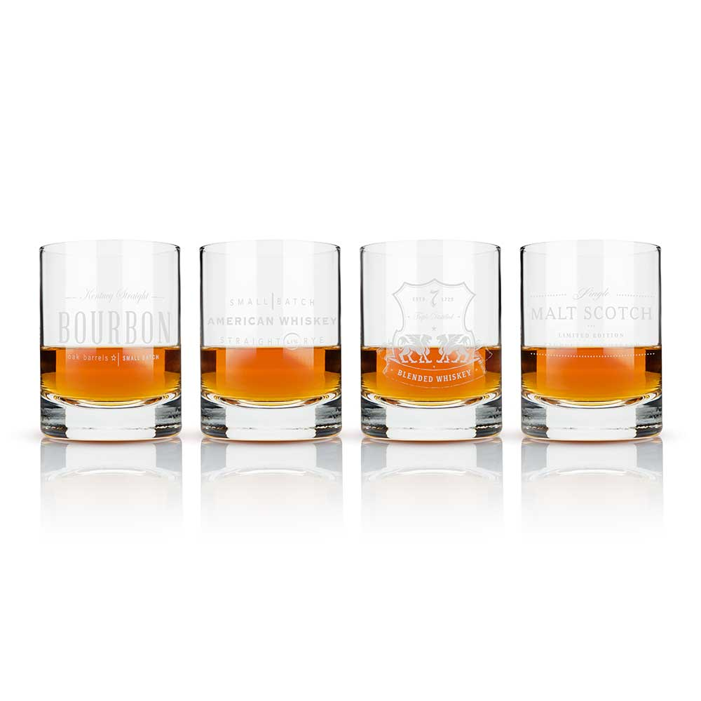 Four etched whiskey label crystal tumblers with liquid contents and a white background