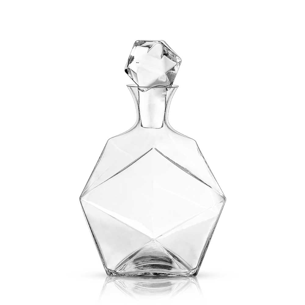 Faceted crystal liquor decanter with a white background